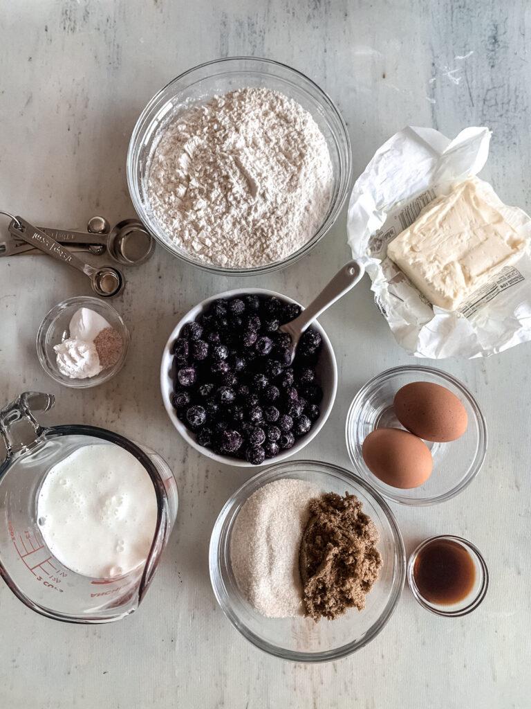 Buttermilk Blueberry Muffin Ingredients in bowls. Butter, sugar, eggs, vanilla, flour, buttermilk, salt, baking powder, baking soda and blueberries