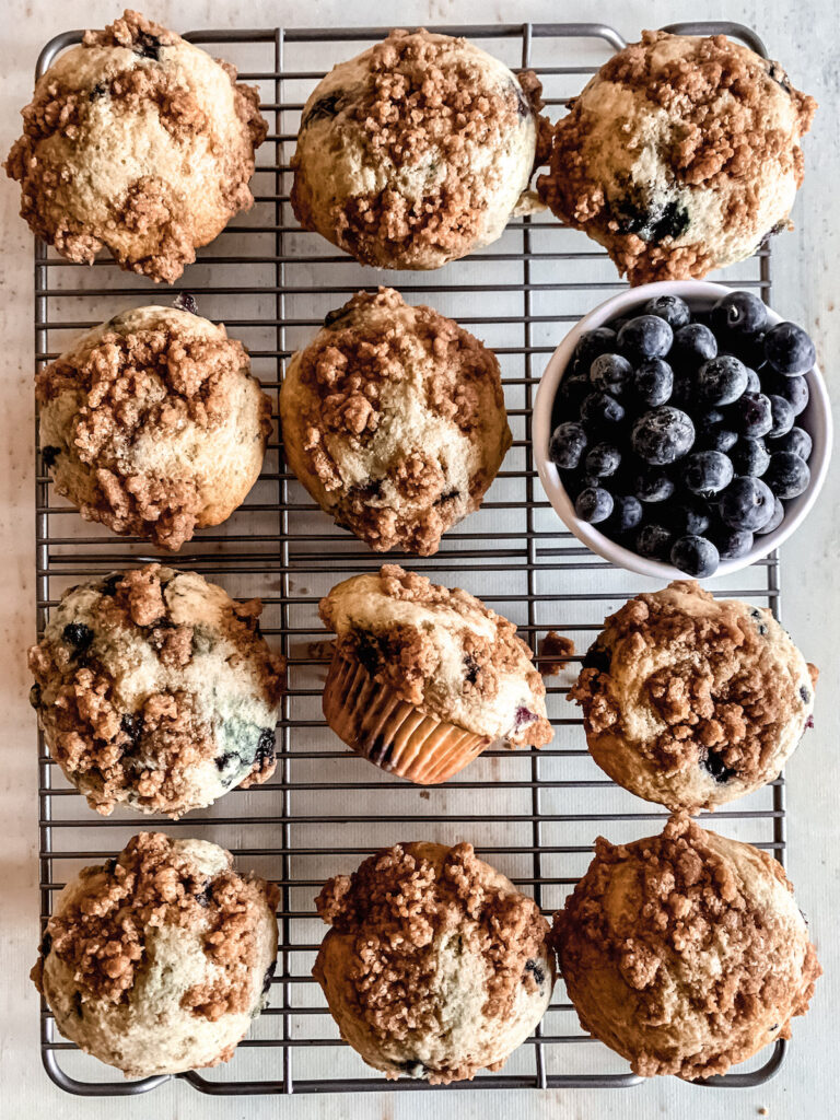 Buttermilk Blueberry muffins on a wire rack with a bowl of blueberries