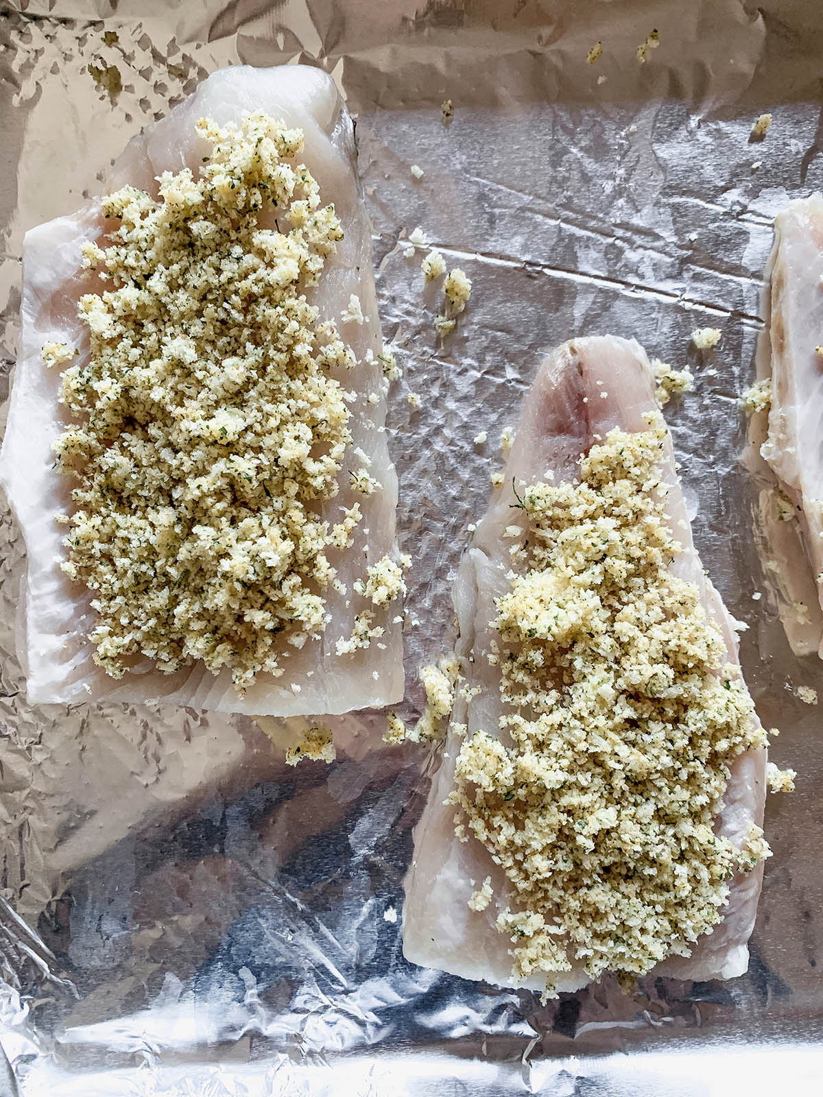Two portions of raw fish with breadcrumb topping on a foil-lined sheet.