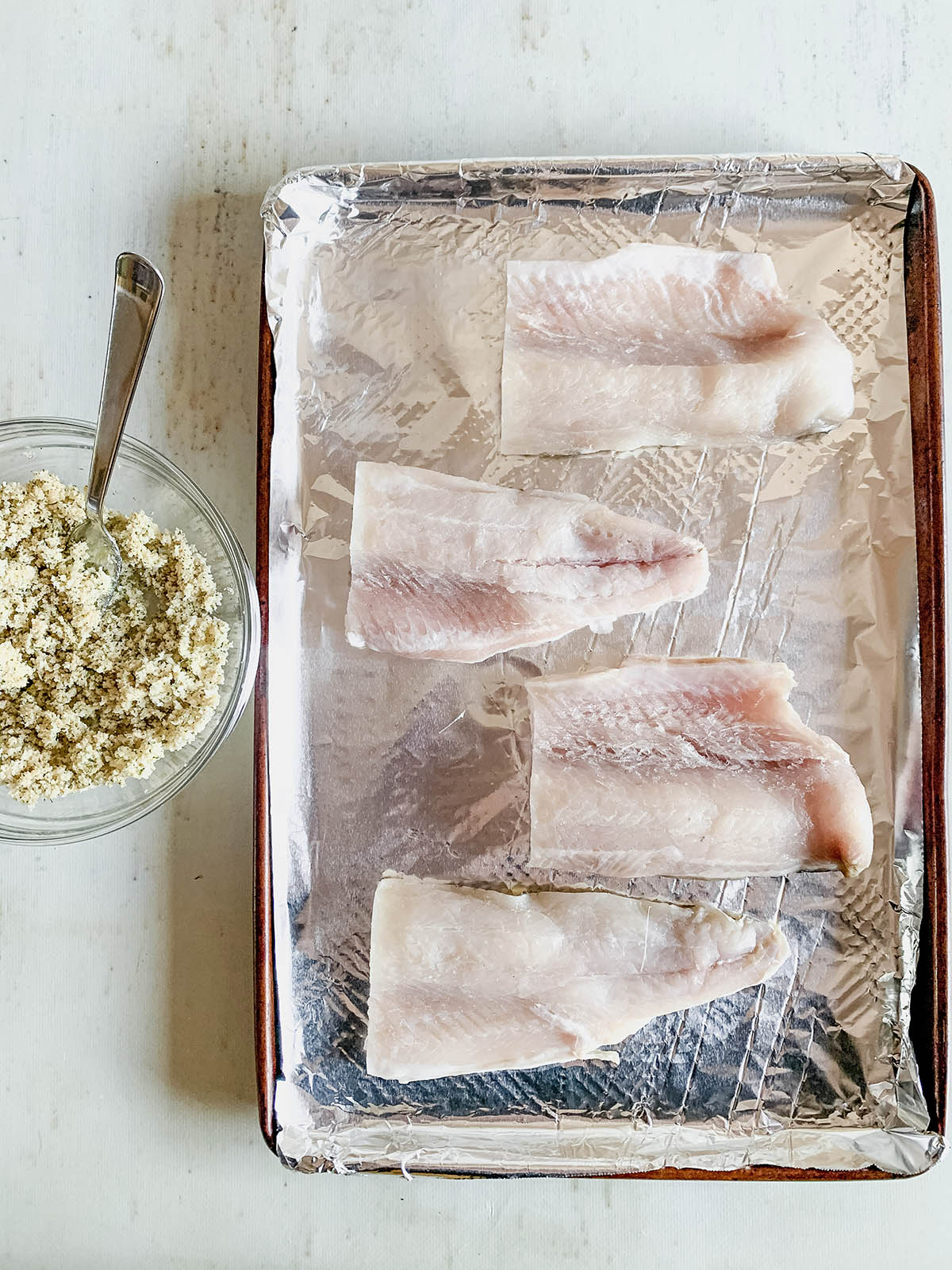 Four raw fish filets on a foil-lined baking sheet next to a bowl of mixed breadcrumbs and spices.