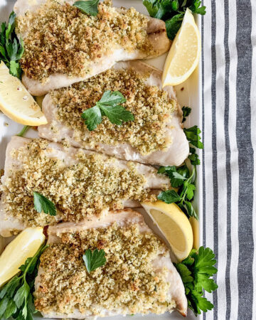 Overhead image of a platter of baked Panko-crusted white fish with parsley and lemon on a striped tablecloth.