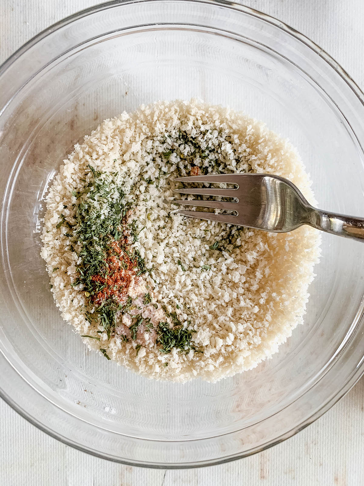 A small bowl with breadcrumbs and spices being mixed with a fork.