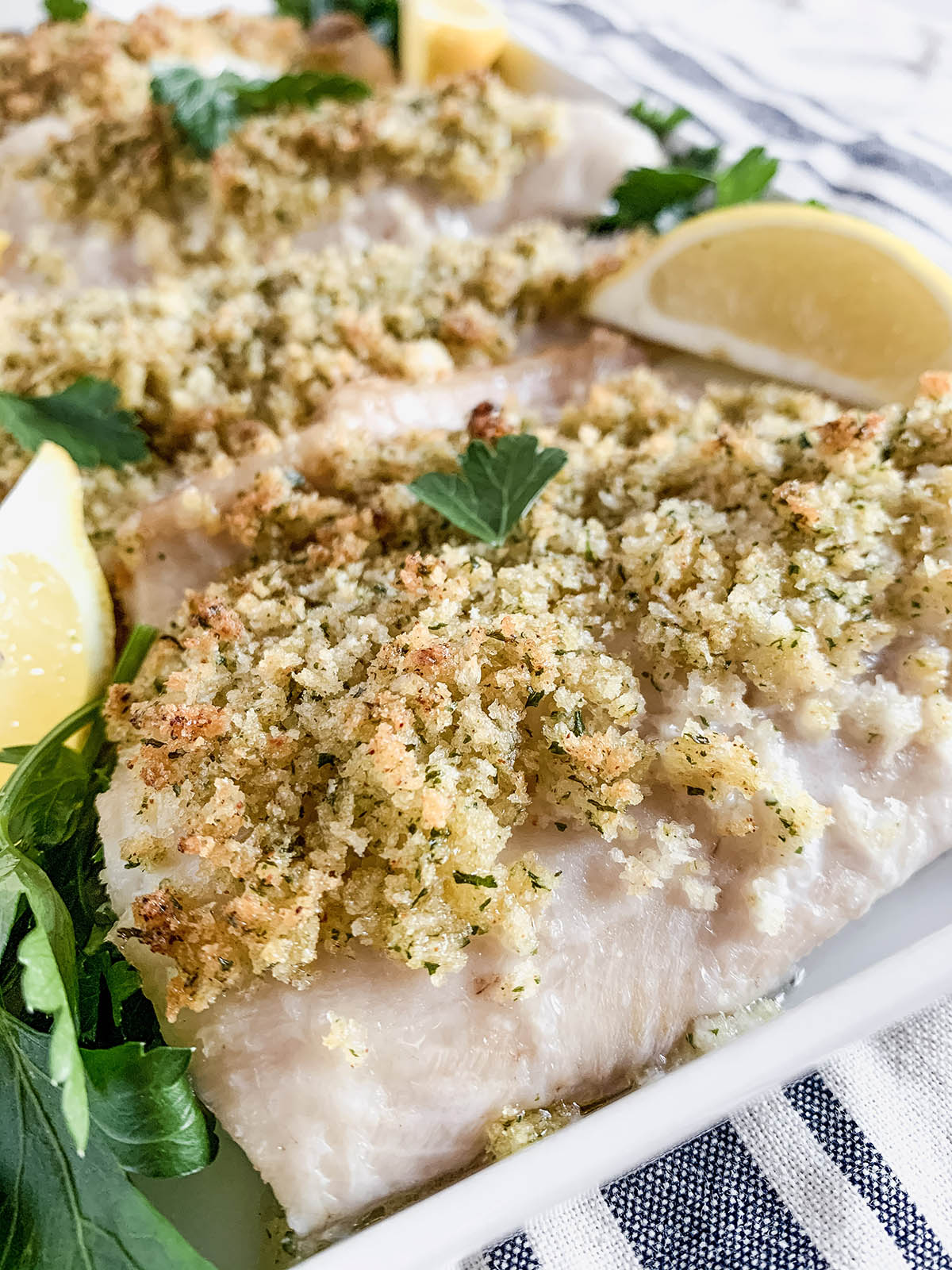 45º image of a portion of baked Panko-crusted whitefish on a platter with lemon wedges and fresh parsley.