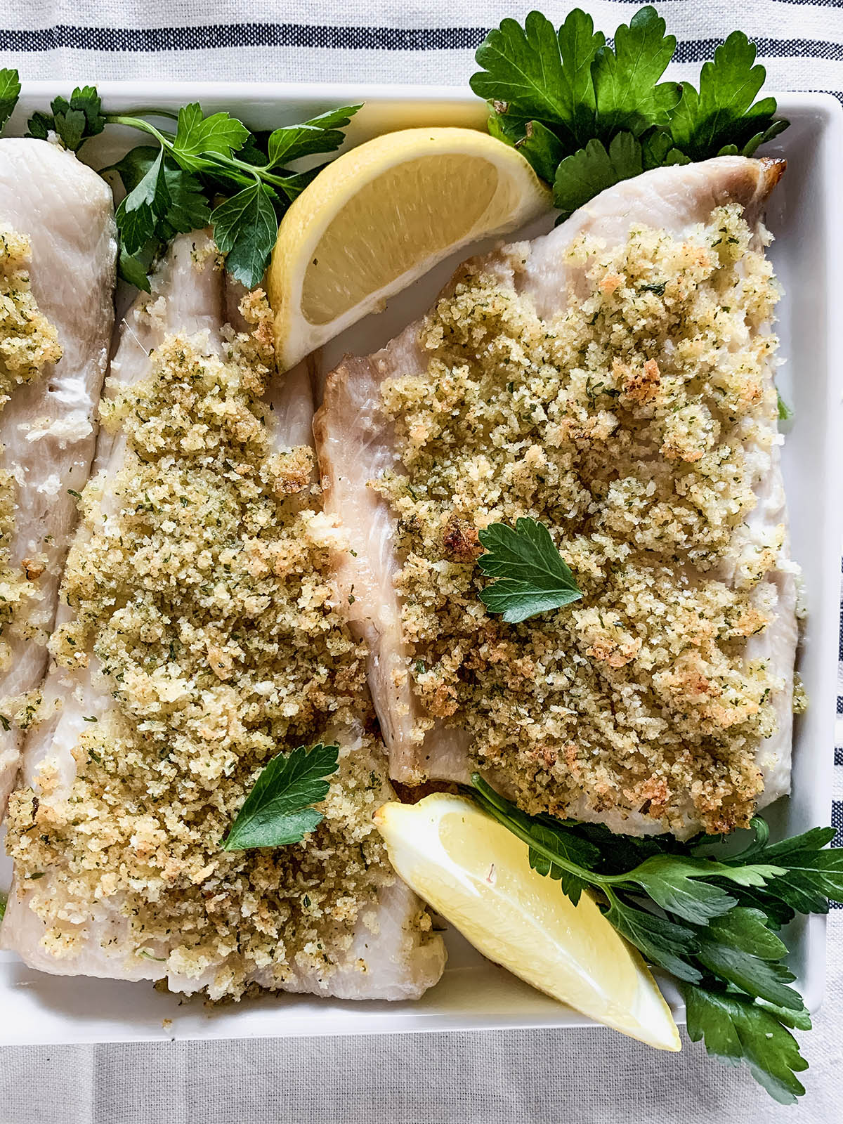 Close up of two portions of baked Panko-crusted white fish on a white platter topped with lemon wedges and parsley leaves.