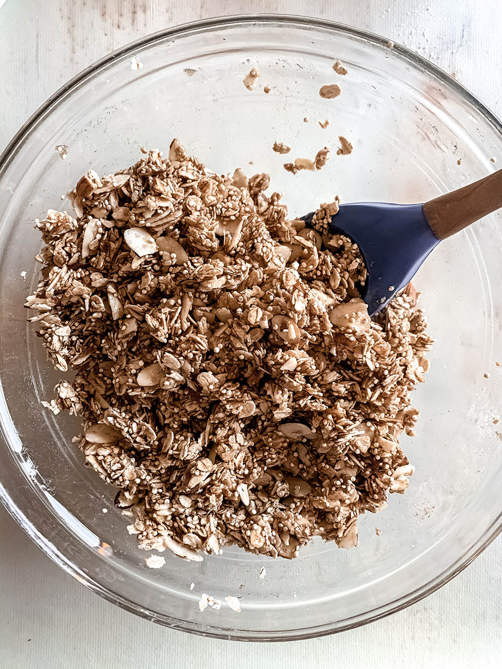Mixed granola before baking in a large glass bowl.