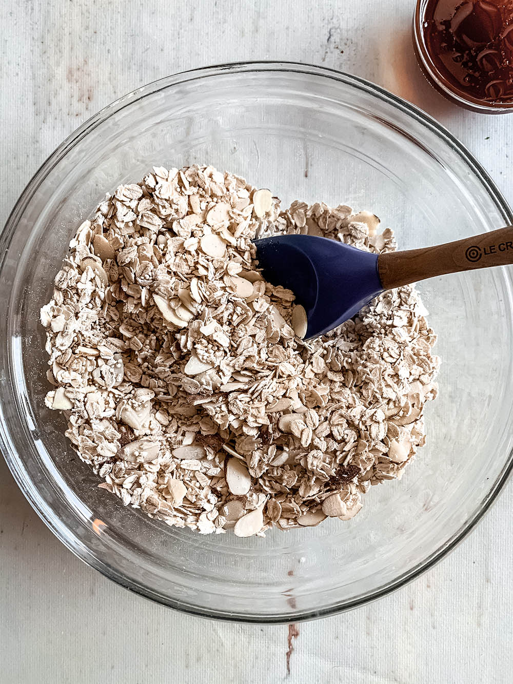 Dry granola ingredients mixed in a glass bowl.