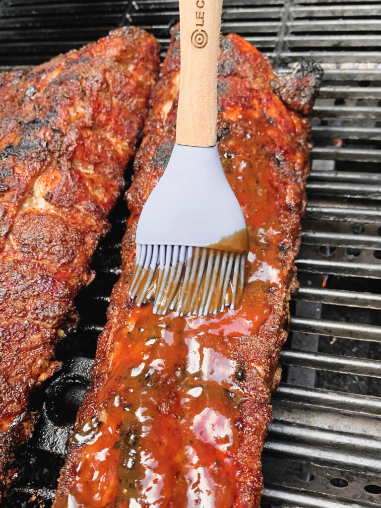 BBQ Baby back ribs on the grill being basted with bbq sauce on a blue silicone brush