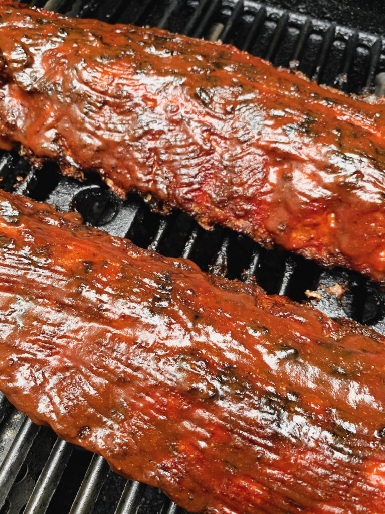 BBQ Baby back ribs on a grill coated in bbq sauce