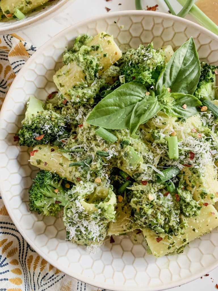Large tube pasta with green sauce and fresh herbs in a white bowl with a honeycomb pattern