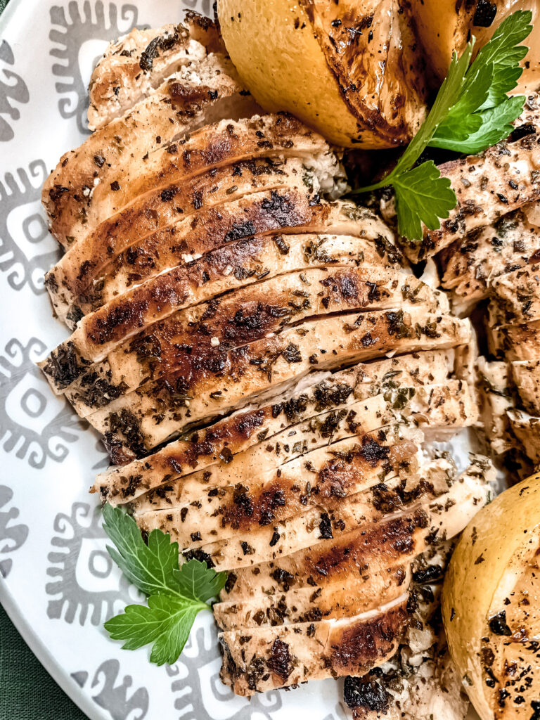 Close up of grilled mediterranean chicken breasts in a patterned bowl with charred lemons and parsley