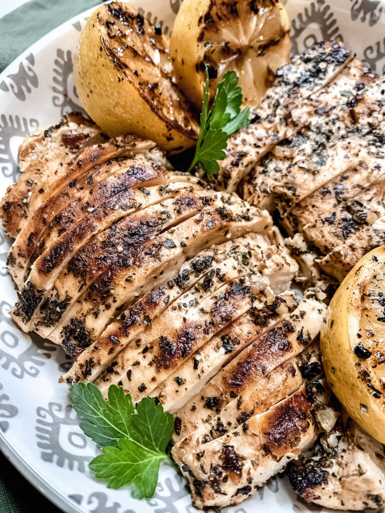 Sliced grilled Mediterranean Chicken breasts in a white patterned bowl with charred lemons and parsely
