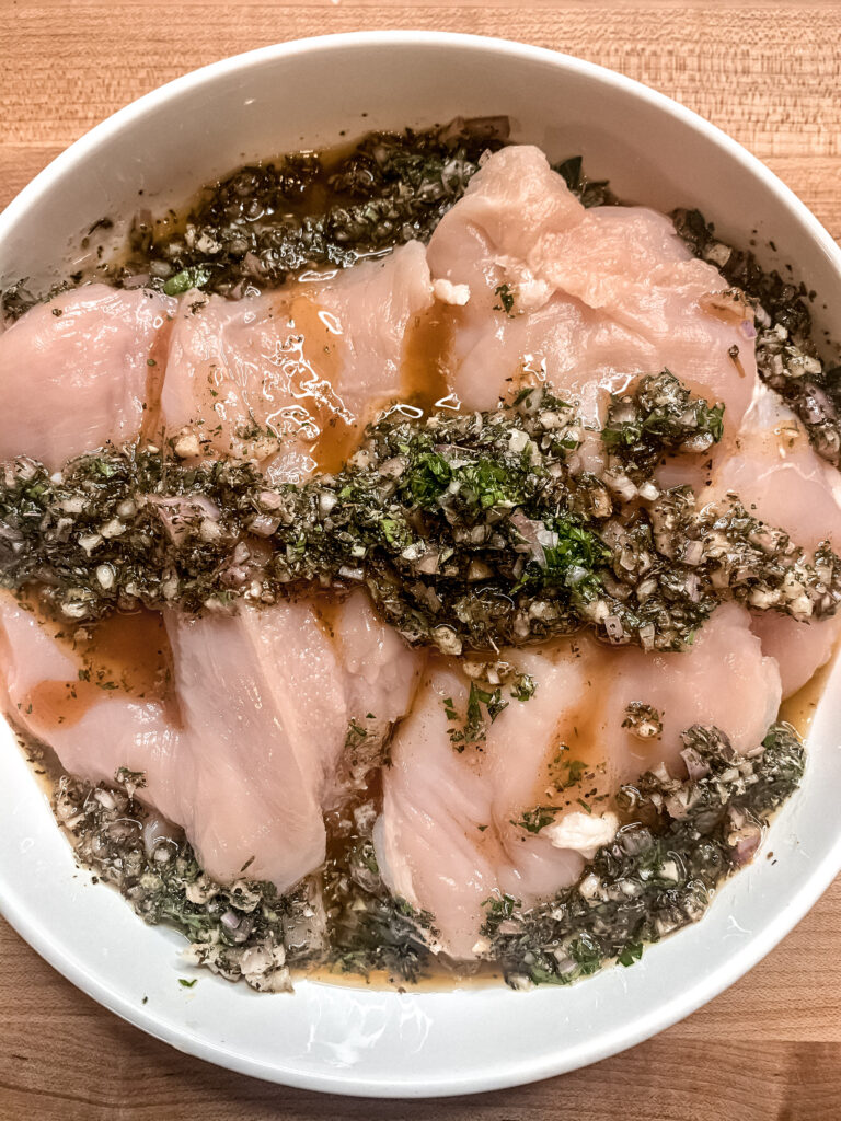 Raw chicken breasts in a shallow white dish with marinade on top.