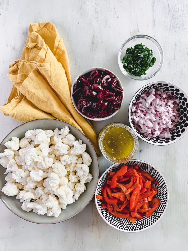 Marinated cauliflower salad ingredients in small bowls. Fresh cauliflower florets, roasted red peppers, minced red onion, sliced kalamata olives, minced parsley and Italian dressing