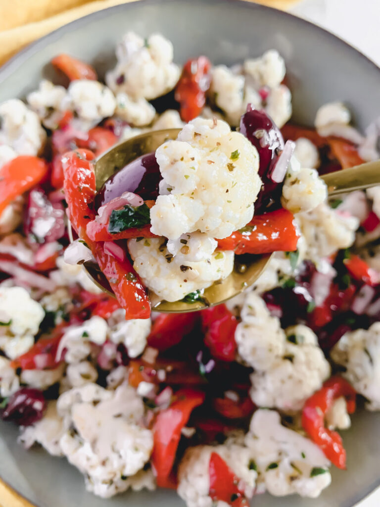 Marinated cauliflower salad with a close up of a spoonful on a gold spoon.