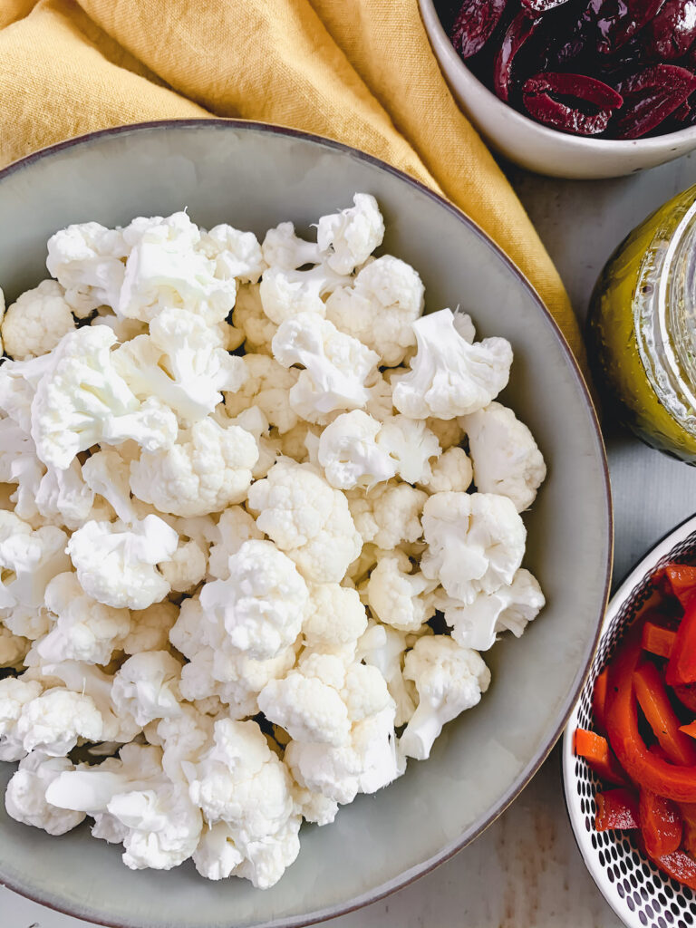 Raw cauliflower florets in a grey bowl with a yellow napkin and bowls of roasted red pepper, italian dressing and olives in the background