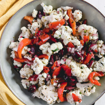 Marinated cauliflower salad with roasted peppers, kalamata olives and red onion in a grey bowl with a yellow napkin