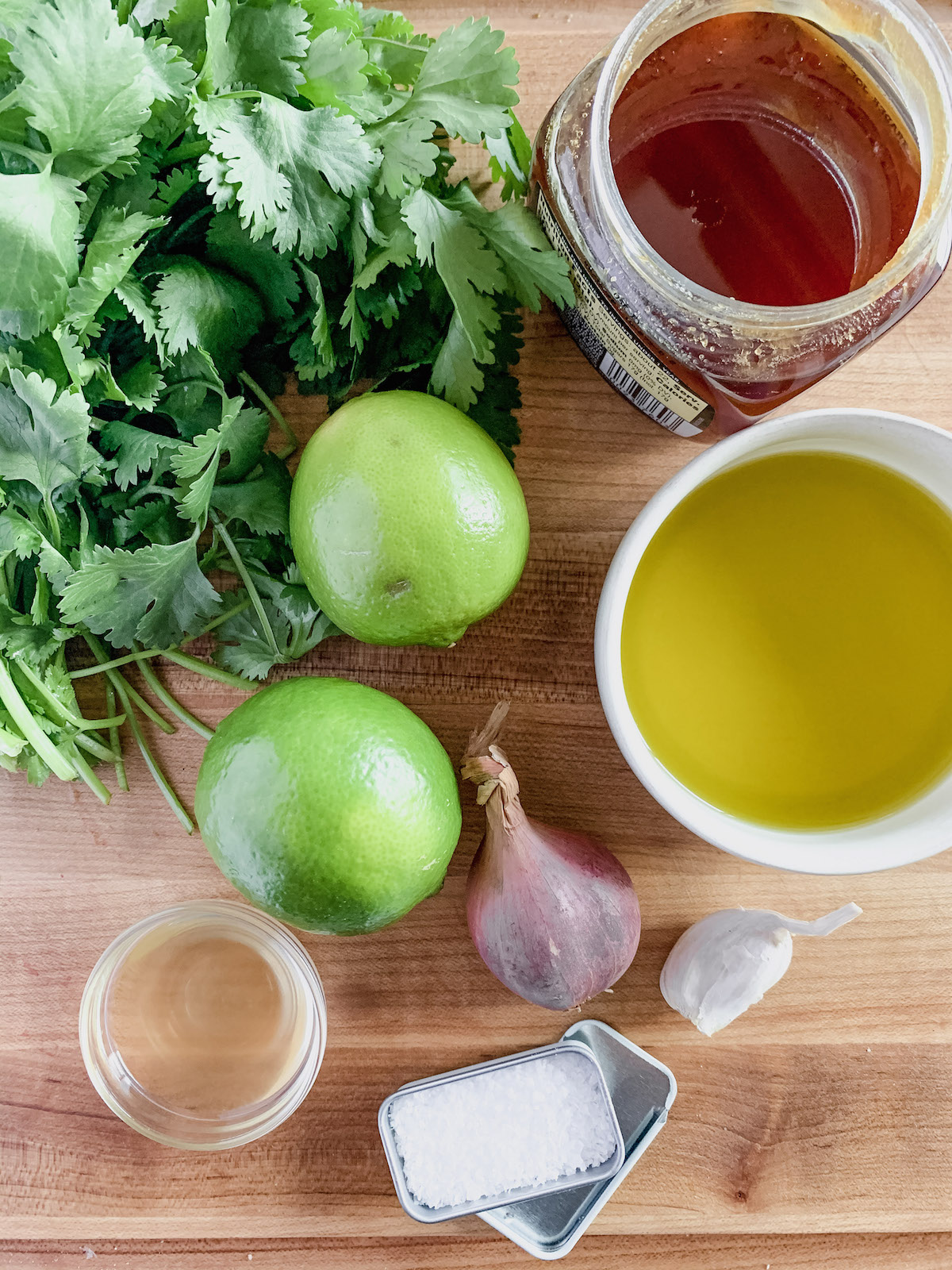 Cilantro lime dressing ingredients on a wood cutting board. A bunch of fresh cilantro, two limes, one shallot, garlic clove, bowl of olive oil, small bowl with vinegar, jar of honey and small tin of salt.