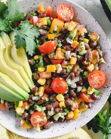 Fiesta salad in a speckled white bowl with sliced avocado and cilantro leaves on top.