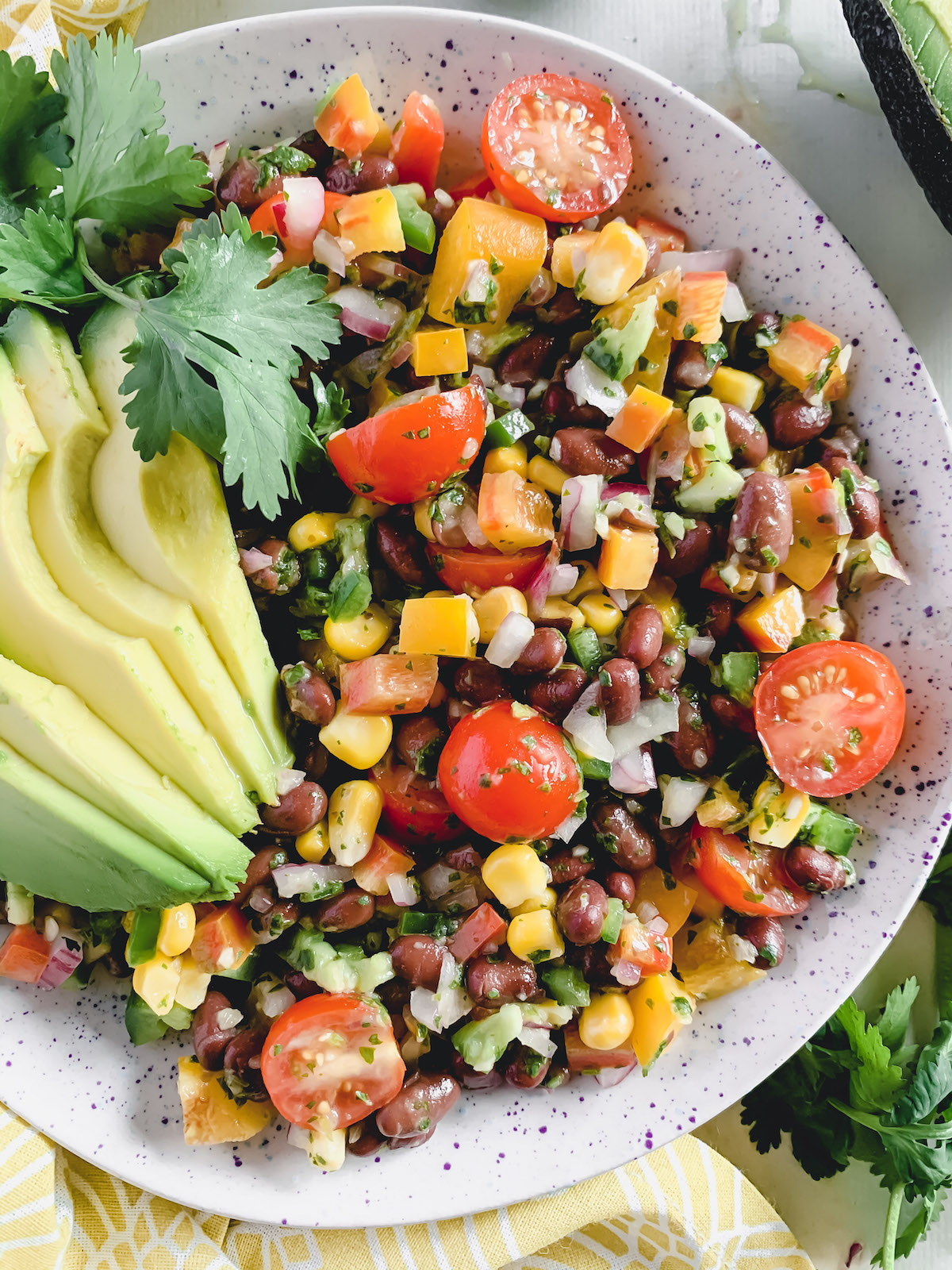 Fiesta salad with avocado slices in a speckled bowl.