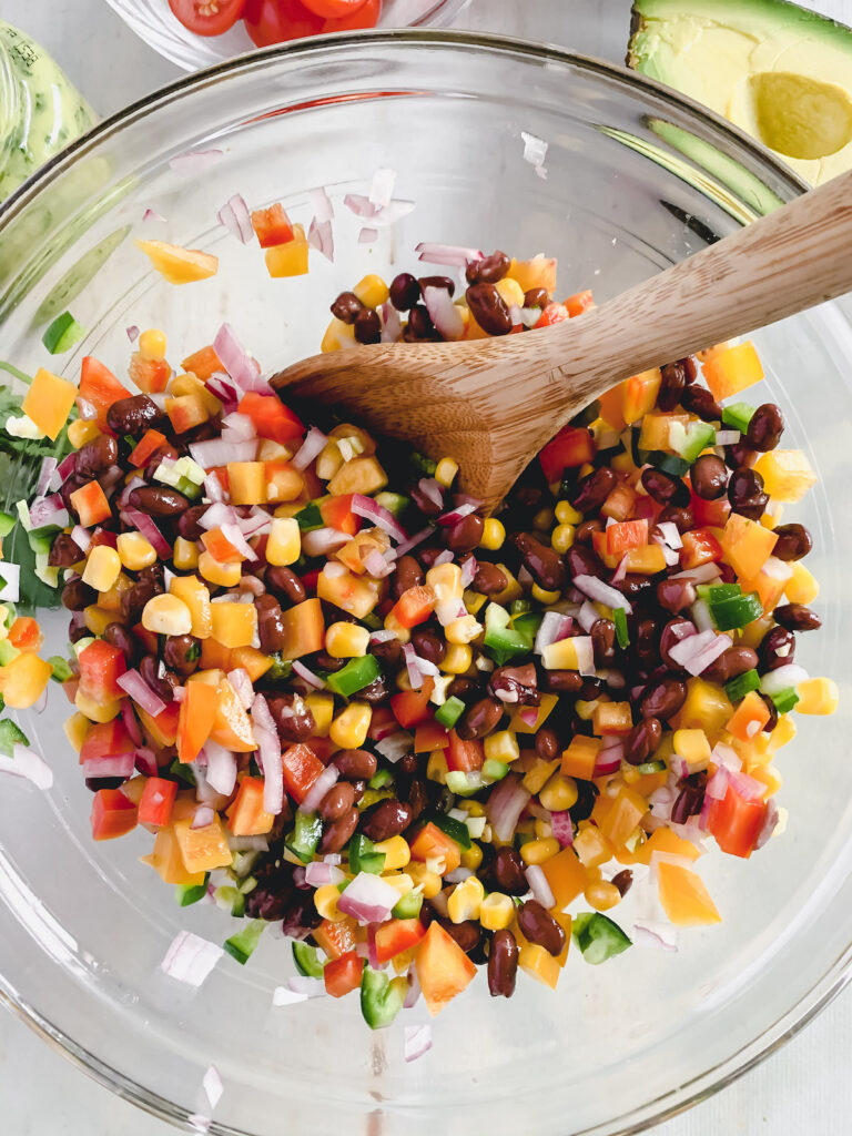Fiesta salad ingredients chopped up in a glass mixing bowl with a wooden spoon.