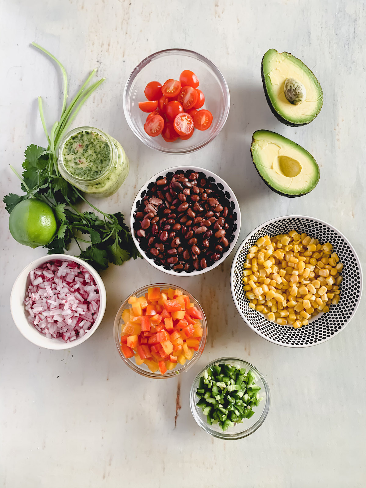 Fiesta salad ingredients on a white background. Black beans, corn, diced red onion, diced peppers all in little bowls. Mason jar with cilantro lime vinaigrette next to bunch of cilantro and fresh lime and an avocado sliced in half.