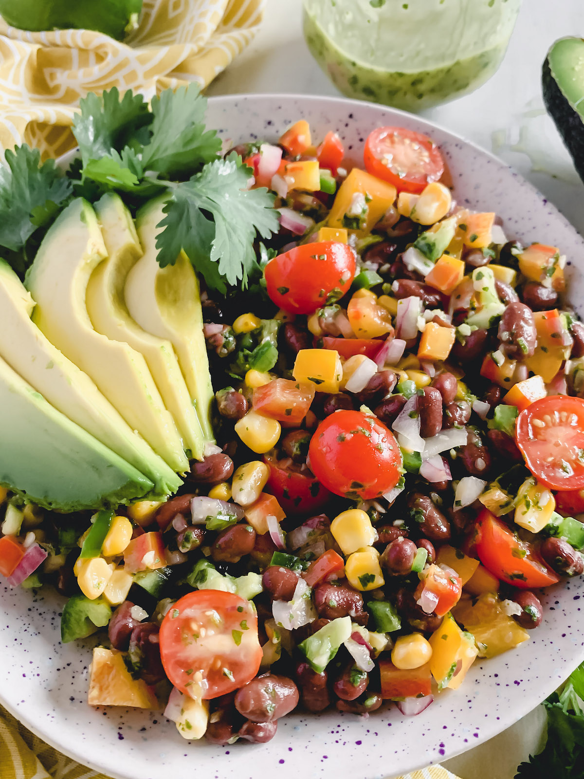 Fiesta salad in a speckled bowl with sliced avocado on top.