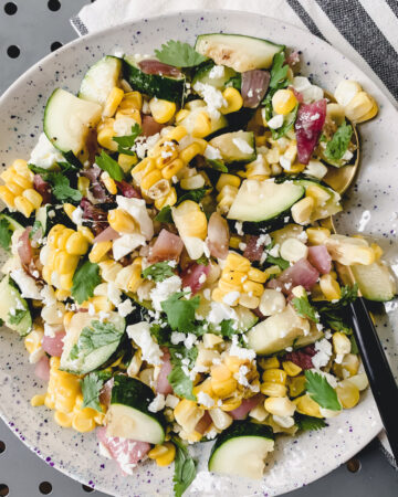 grilled corn, zucchini, red onion, feta and herbs chopped and mixed together in a speckled dish
