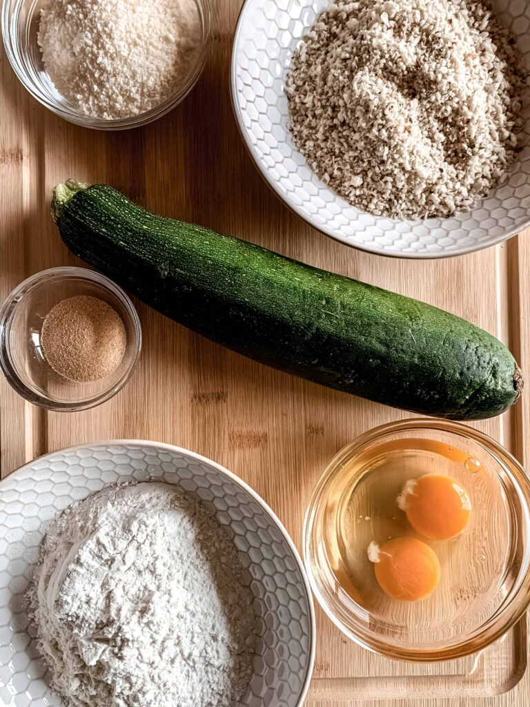 Ingredients for garlic parmesan air fryer zucchini fries on a wood cutting board. Large zucchini, two eggs cracked in a glass bowl, flour, parmesan cheese, panko bread crumbs and garlic powder.