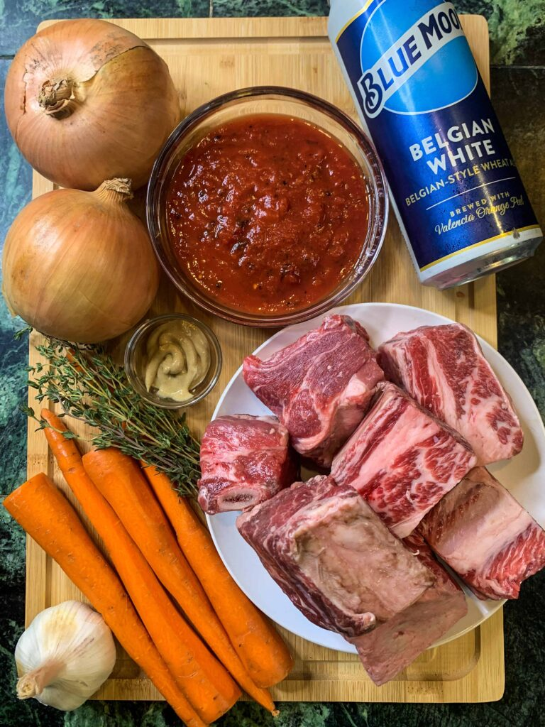 Wood cutting board with plate of raw beef short ribs, carrots, onions, garlic, fresh thyme, mustard, crushed tomatoes and a can of beer.