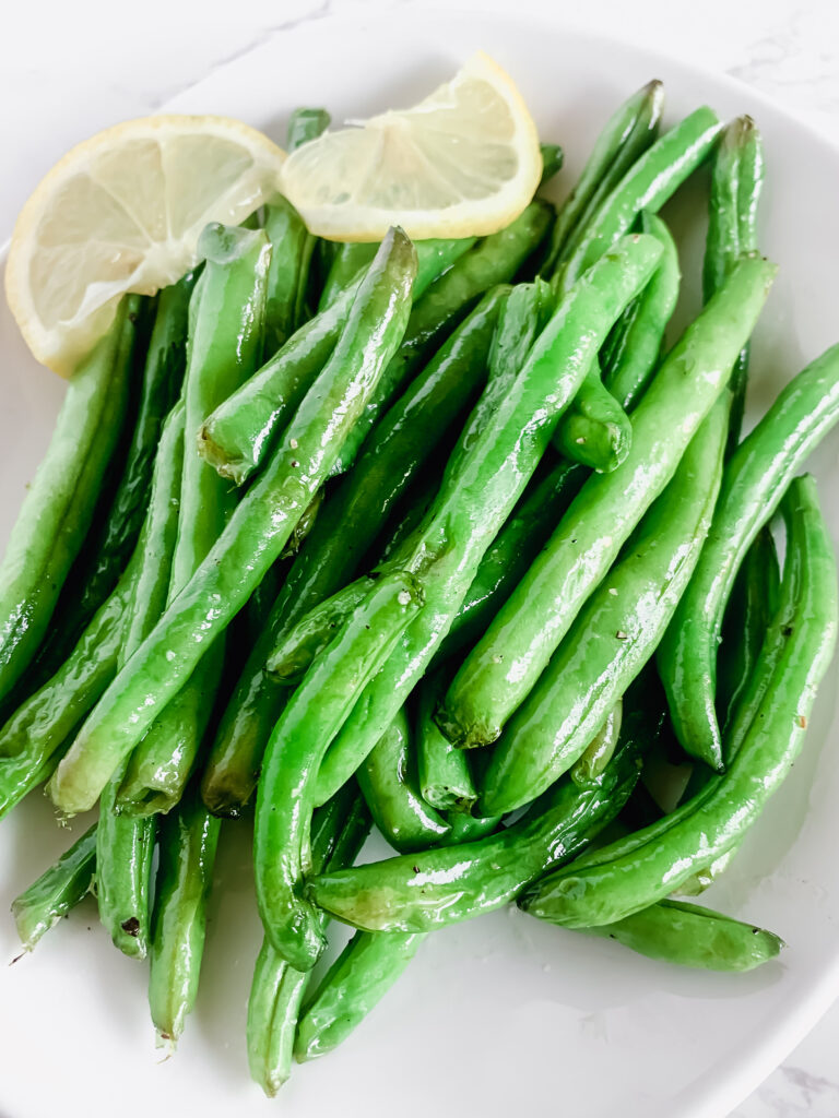 Air fried green beans with a slice of lemon twist on a white plate.