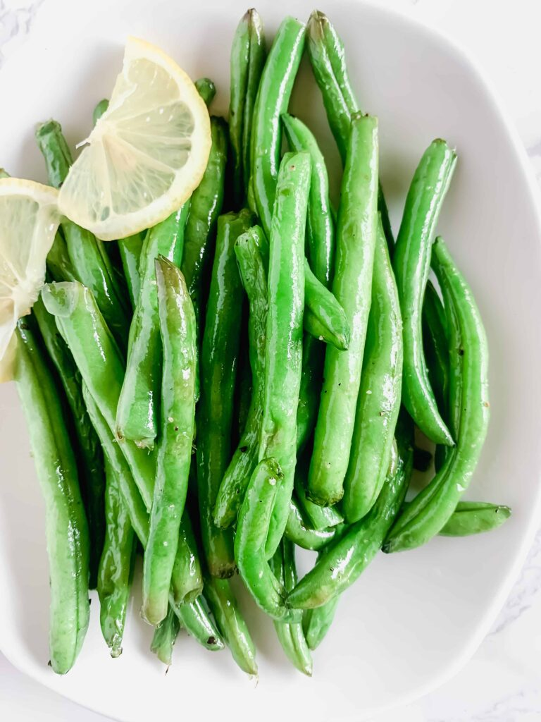 Air fried green beans on a white plate with a lemon twist