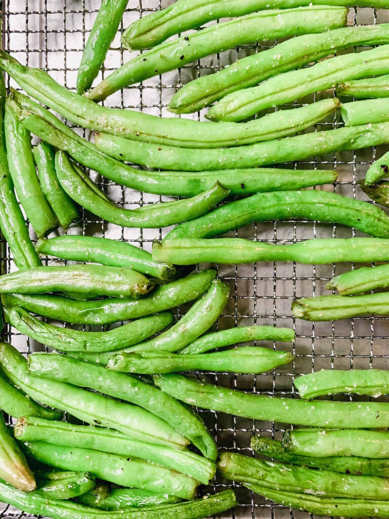 Air fried fresh green beans in the basket of an air fryer oven.