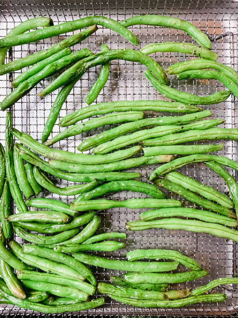 Air fried green beans in the basket of an air fryer oven.
