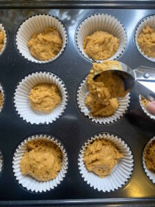Spiced pumpkin muffin batter being scooped into lined muffin tin with an ice cream scoop.