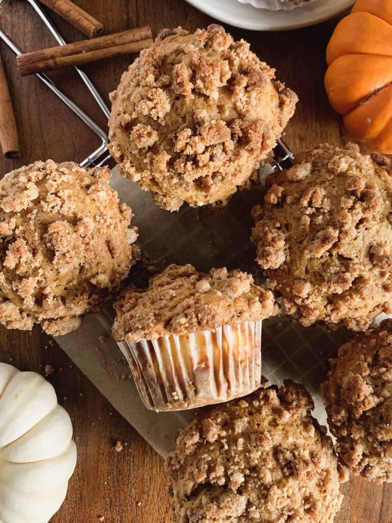 Spiced pumpkin cream cheese muffins with cinnamon streusel topping on a wire rack with parchment paper and mini pumpkins in the background.