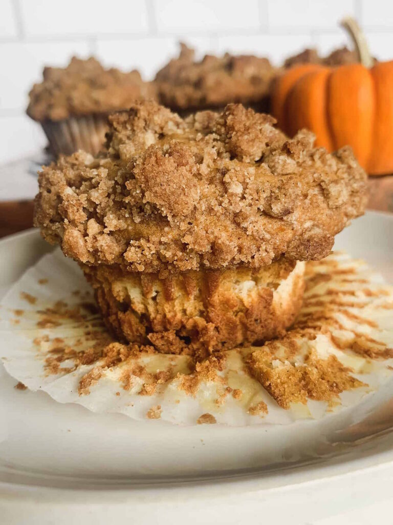 Spiced pumpkin cream cheese muffin with cinnamon streusel topping on a peeled muffin wrapper with muffins and a mini orange pumpkin in the background.