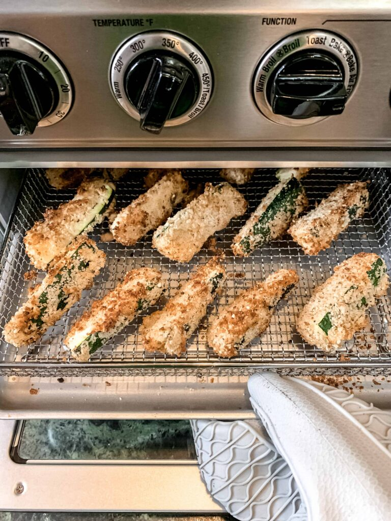 Crispy golden brown zucchini fries coming out of the air fryer oven.