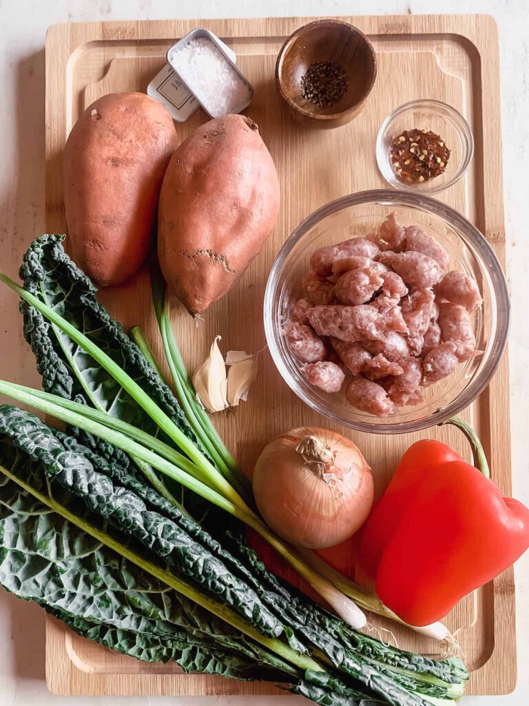 Ingredients for sweet potato breakfast hash on a wood cutting board. Sweet potatoes, kale, onion, pepper, garlic, sausage, red pepper flakes, salt and pepper.