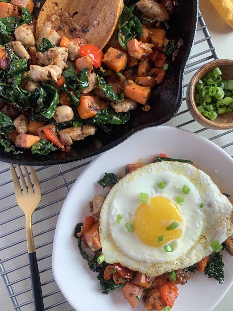 Sweet potato breakfast hash on a white plate topped with a fried egg next to a blue skillet and small bowl of chopped scallions.