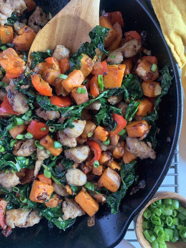 Sweet potato breakfast hash being scooped up with a wooden spoon out of a blue cast iron skillet.
