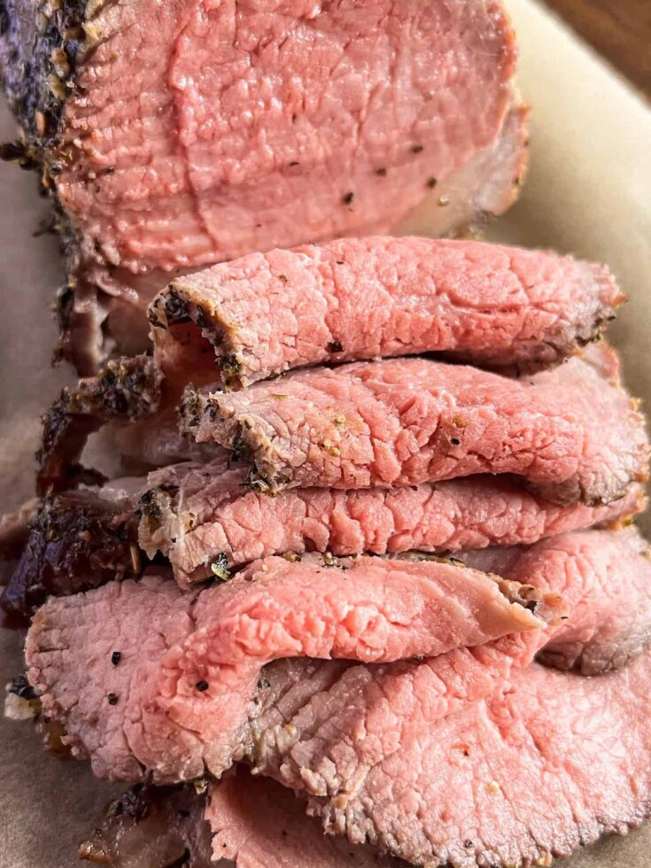 Close up of slices of eye of round roast beef on brown parchment paper.