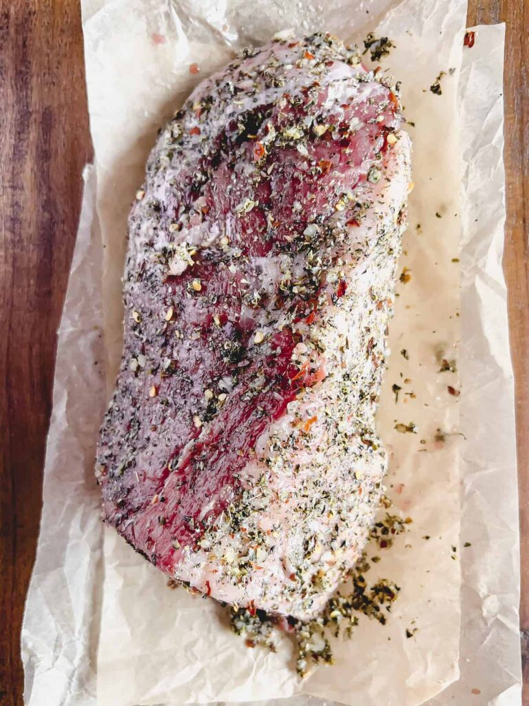 Raw roast covered in garlic herb seasoning on brown parchment paper on a wood board.