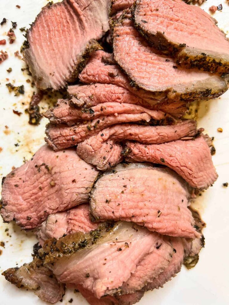 Thinly sliced roast beef on a white cutting board.