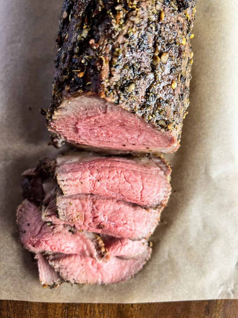 Overhead view of thinly sliced eye of round roast beef cooked rare on brown parchment on wood board.