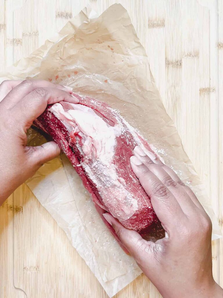 Brown hands rubbing salt into raw meat on a wood cutting board.
