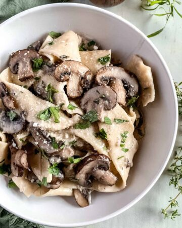 White bowl full of pappardelle with mushrooms and creamy garlic parmesan sauce with fresh herbs in the background.