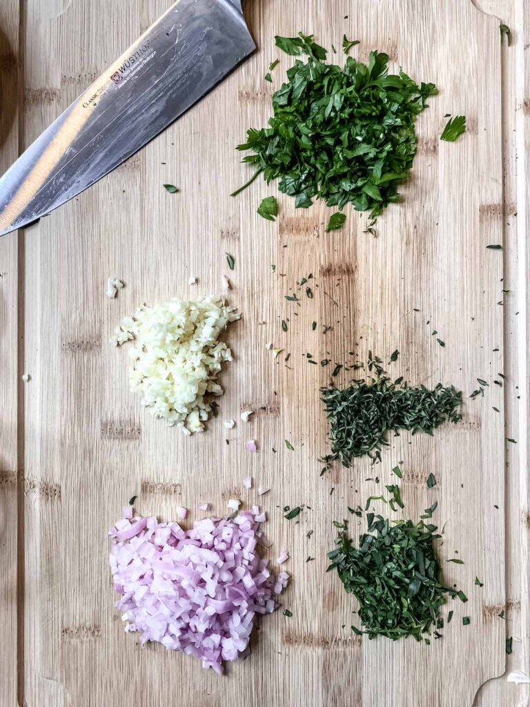 Minced garlic and shallots and finely chopped fresh herbs on a wood cutting board with a knife.