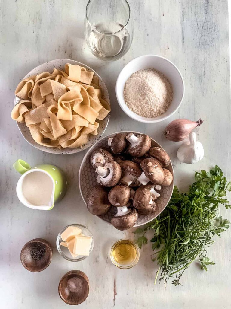 Ingredients for recipe in small bowls. Pappardelle pasta, parmesan cheese, white wine, butter, garlic, olive oil, heavy cream, shallots and fresh herbs.
