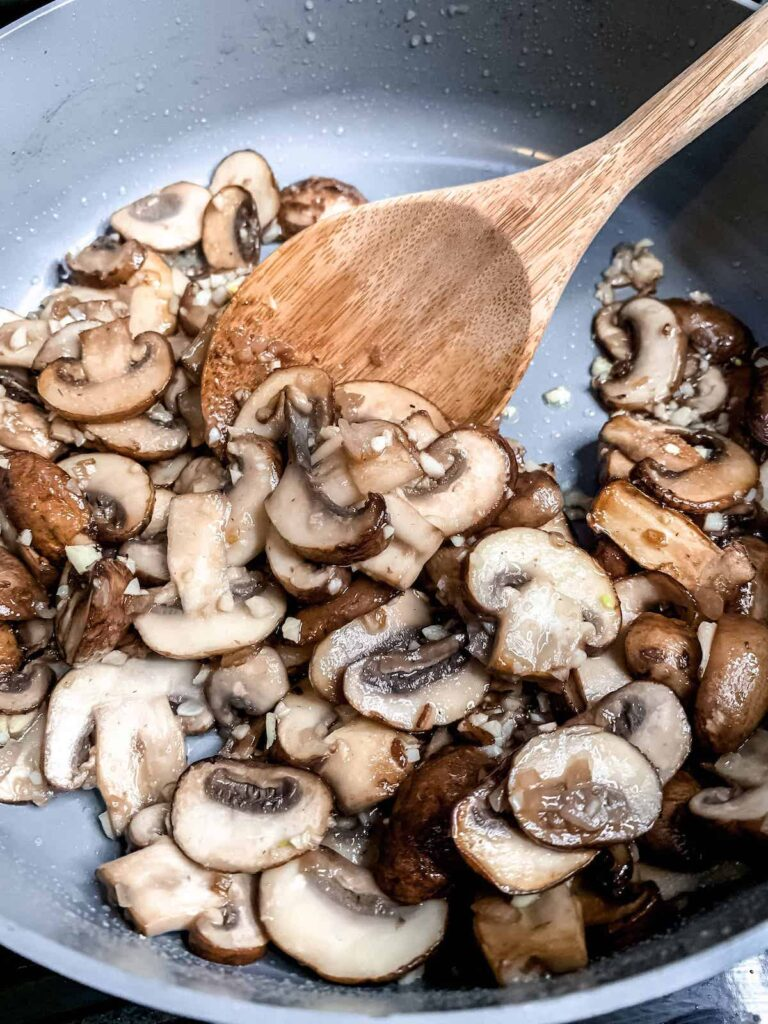 Saute pan with garlic butter mushrooms and fresh thyme and a wooden spoon.